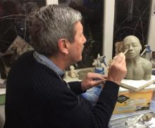 Student sculpting with clay, and making a small  portrait bust