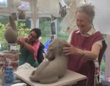 two termly students  sculpting a lion and an abstract form