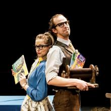 Two people stand back to back holding books from Roald Dahl