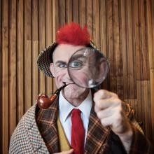 Tweedy the clown looks through a magnifying glass