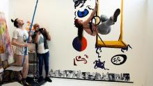 Photo of acrobat on trapeze and 2 men with cameras © Beatrix Haxby