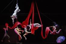 Cabaret performers hang from red silks in various dance positions